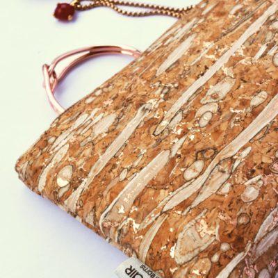 Clutch aus Fenchel und Kork von Bag Affair in Detailansicht mit Schmuck in Rose-Gold