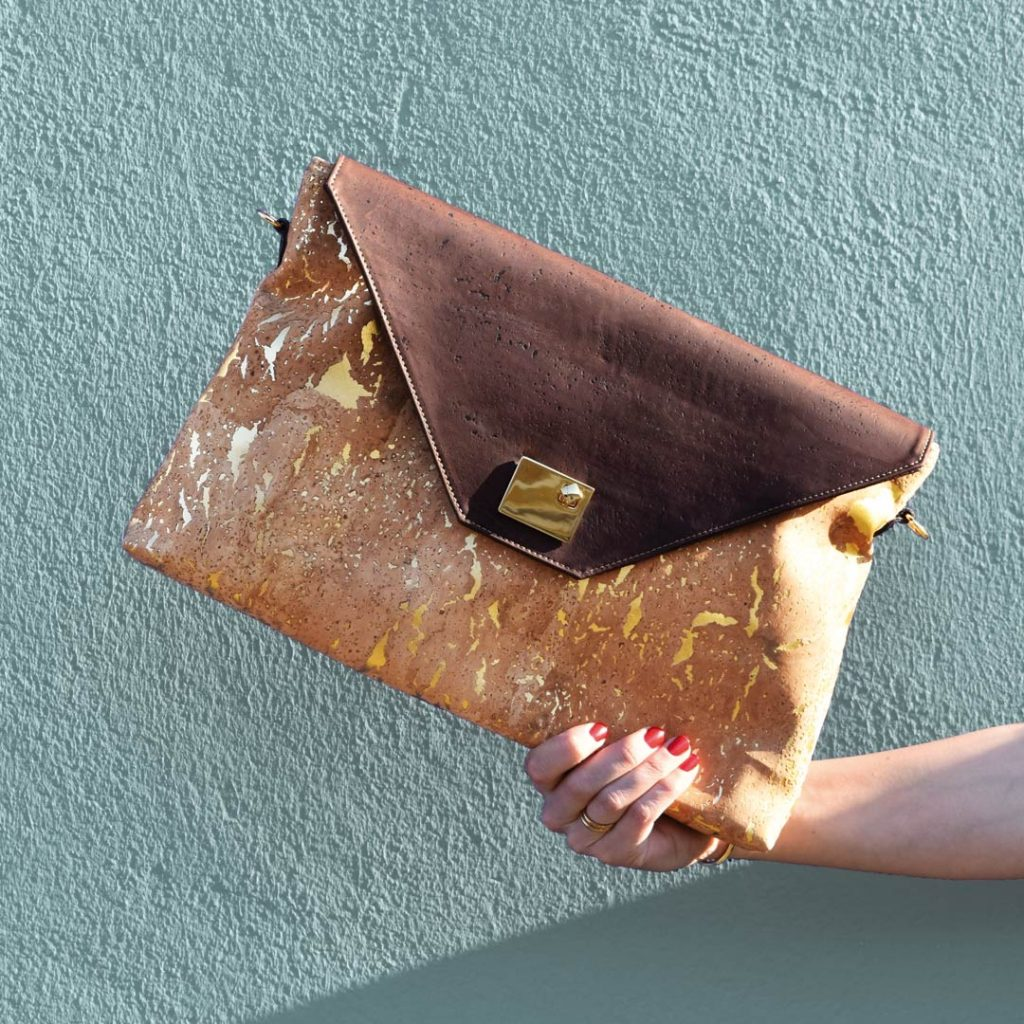 Laptop bag Sassy in gold-natural and brown, held by a hand in front of a blue-grey background