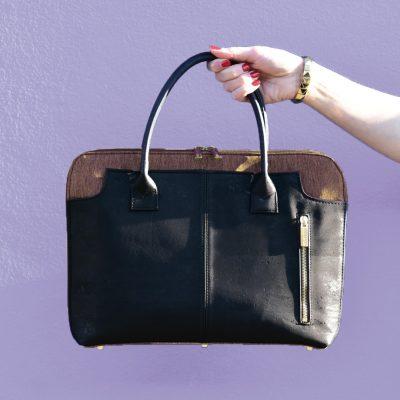 Savvy Business-Tasche aus schwarzem und braunem Kork, die von einer Hand vor einer lila Wand gehalten wird