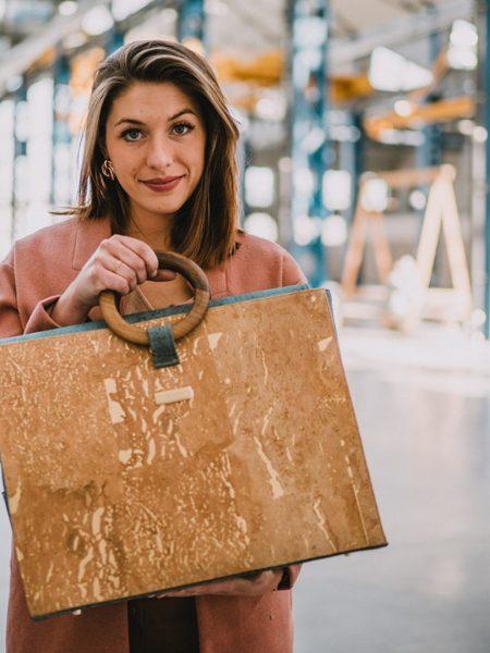 Bossy Handtasche, getragen von einem Model an den Griffen aus Walnussholz dieser einzigartigen Business-Tasche