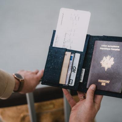 Fokus auf die schwarz-marine Passhülle aus Kork, die über einem Gepäckstück gehalten wird