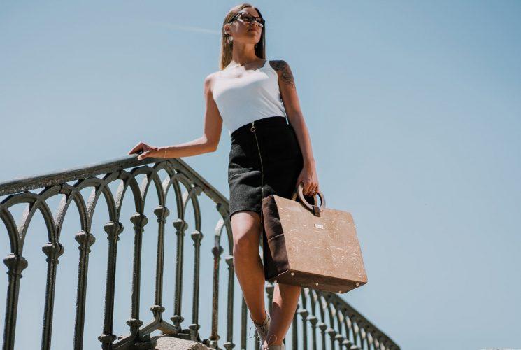 Bossy Aktentasche aus gold-natürlichem und braunem Kork, getragen von einer schwarz-weiß gekleideten Frau, die vor dem blauen Himmel die Treppe hinuntergeht