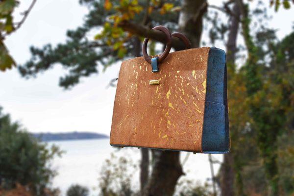 Bossy Tasche in natur-gold und grünem Kork, welche mit den runden Holzgriffen über einem Ast vor dem Meer hängt