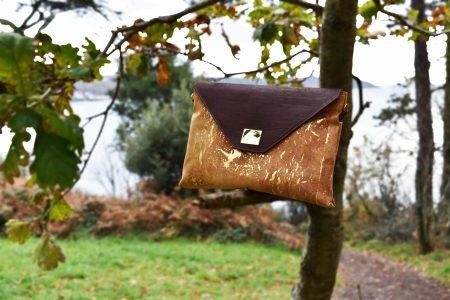 Sassy Business-Tasche gold-natürlich und braunen Kork auf einem Ast eines Baumes vor Natur und Meer platziert