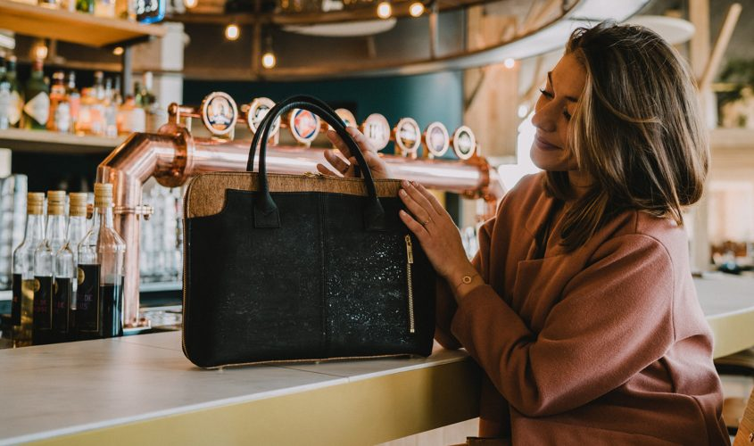 Business-Tasche Savvy auf einer Bar, gehalten und von einem Modell in rosa Mantel berührt