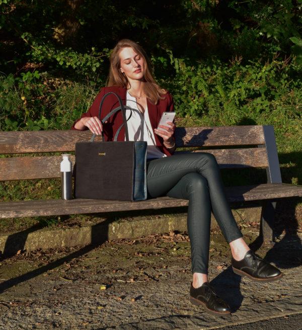 Modell auf einer Bank in der Natur mit Classy Business-Tasche in Schwarz und Grün links von ihr