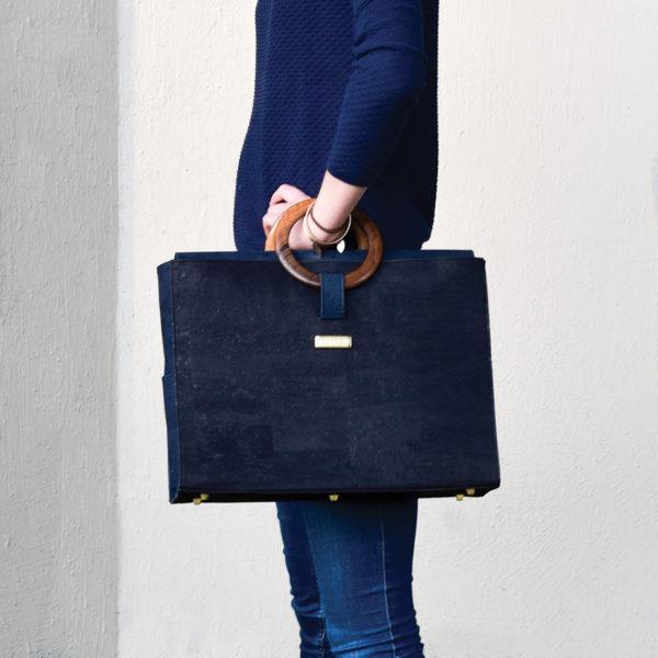 Bossy Aktentasche, die über das Handgelenk getragen und an die Seite des Körpers gehalten wird