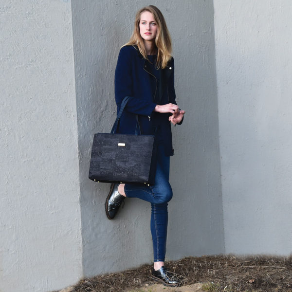 Classy Tasche, die ein Model über den Arm trägt und an eine graue Wand lehnt